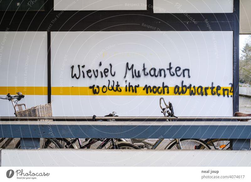 Graffiti – Thema Corona – auf einer weißen Wand mit gelbem Streifen Krise Covid Wut Meinung Kommentar Pandemie Spruch Schrift Handschrift Virus Gesundheit