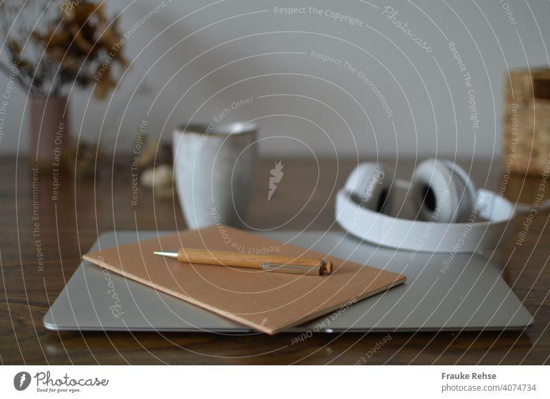 Schreibtisch mit Laptop, Notizbuch, Kugelschreiber im Vordergrund -  Kopfhörer und Becher, Ablage und Blumen im Hintergrund Home Office Notebook Arbeitsplatz