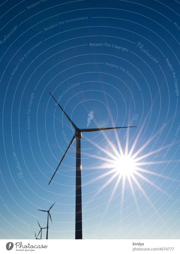 Windkraftanlage. Windräder zur Stromerzeugung vor blauem Himmel mit strahlender Sonne Windenergie Wolkenloser Himmel Sonnenstrahlen Erneuerbare Energie Windrad