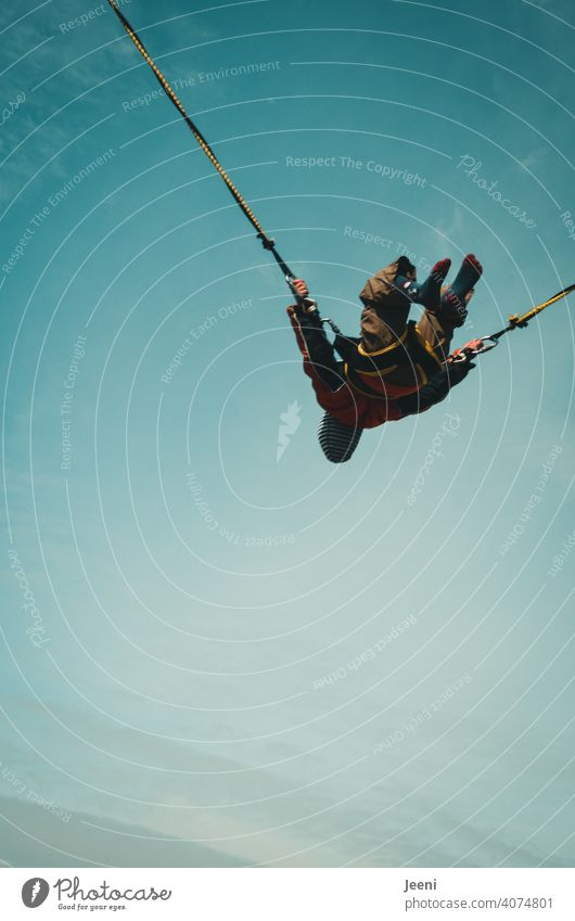 Hoch hinaus | Kind springt Bungee Trampolin springen Spielen spass Spaß haben bungeejump Bungee Anlage Bungee Sprung ein 1 Himmel Blauer Himmel Seil Gummi