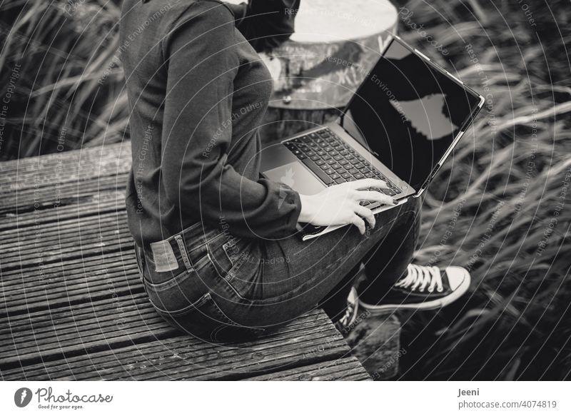 Junge Frau arbeitet draußen (unabhängig vom Ort) auf einem Holzsteg an der frischen Luft am Laptop / PC Computer arbeiten Arbeitsplatz Arbeitswelt