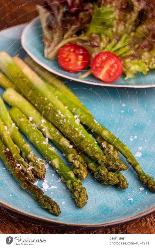 gegrillter grüner Spargel auf einem blauen Teller Planke Holz Saison saisonal Gourmet String Küche Zutaten Spargelstange Lebensmittel Stiel Frische rustikal