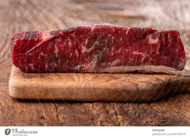 Rohes Steak auf Olivenholz Rindlende Lendenstück Textur www. Medaillon Fett Trocknung mignon Filet Holzplatte roh Trockenheitssteak seitenansicht flämisch angus