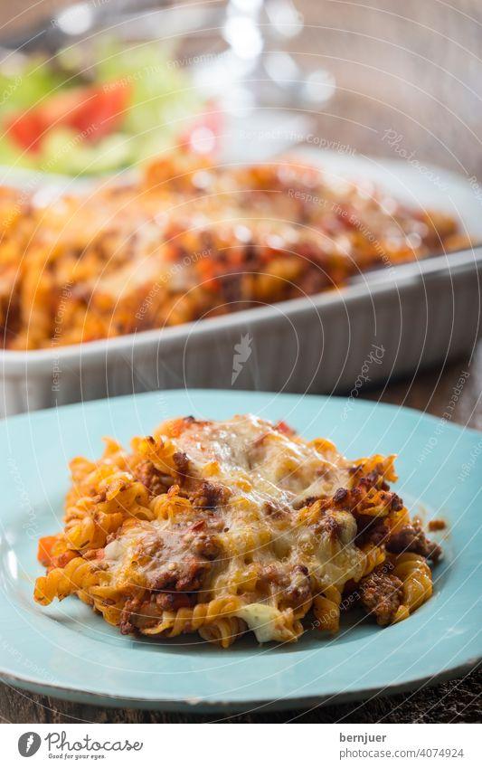 gratinierte Pasta mit Salat auf Holz rigatoni gebacken Käse rustikal Auflauf Sauce Tomaten Bolognaise Fleisch Essen ragu hausgemacht italien Parmesan bolognese