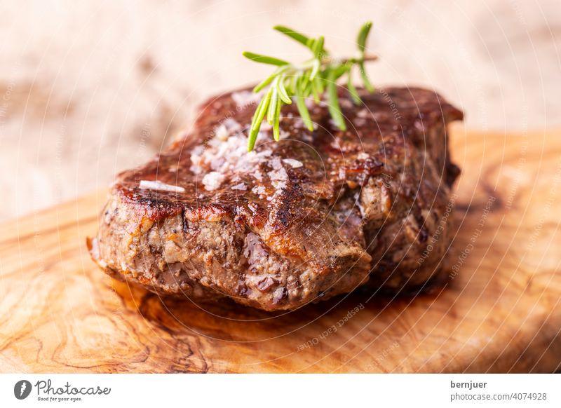 gegrilltes saftiges Steak auf Olivenholz Fleisch Rindfleisch Rosmarin Barbecue schwarz tenderloin rippe Filet Mahlzeit Grillen Essen Brett Messer Rindersteak