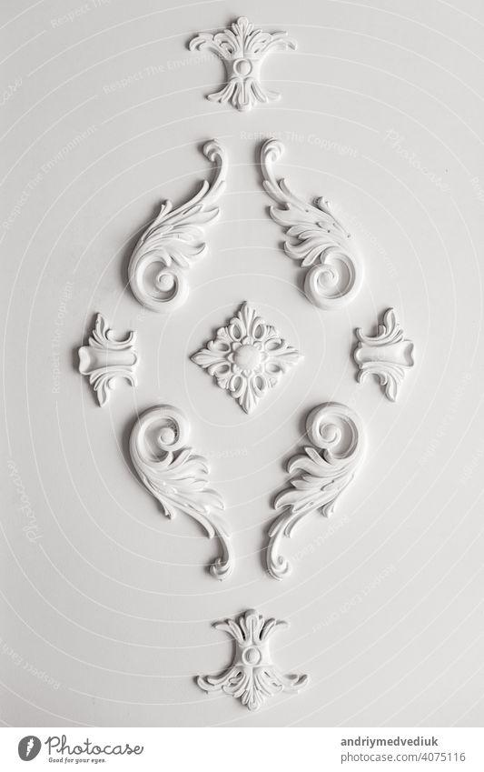 Teures Interieur. Gipsdekor an der Wand. Stuckelemente auf heller Luxuswand. Weiß gemustert. Leistenelement aus Gips. Rokoko-Stil Muster altehrwürdig verziert