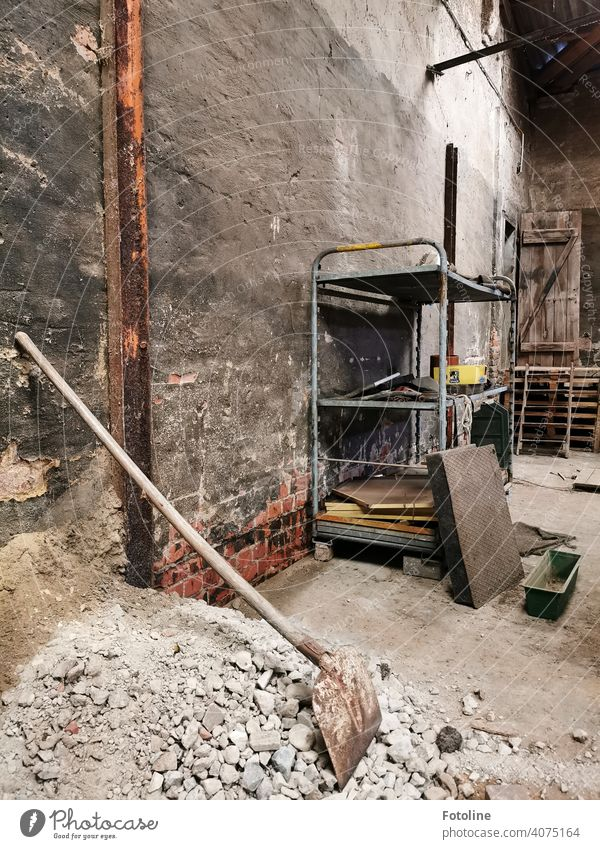 Lost - Teil einer alten Fabrikhalle mit Regal, einem ollen Schutthaufen und einer Schaufel lost places Architektur verfallen Zahn der Zeit Endzeitstimmung