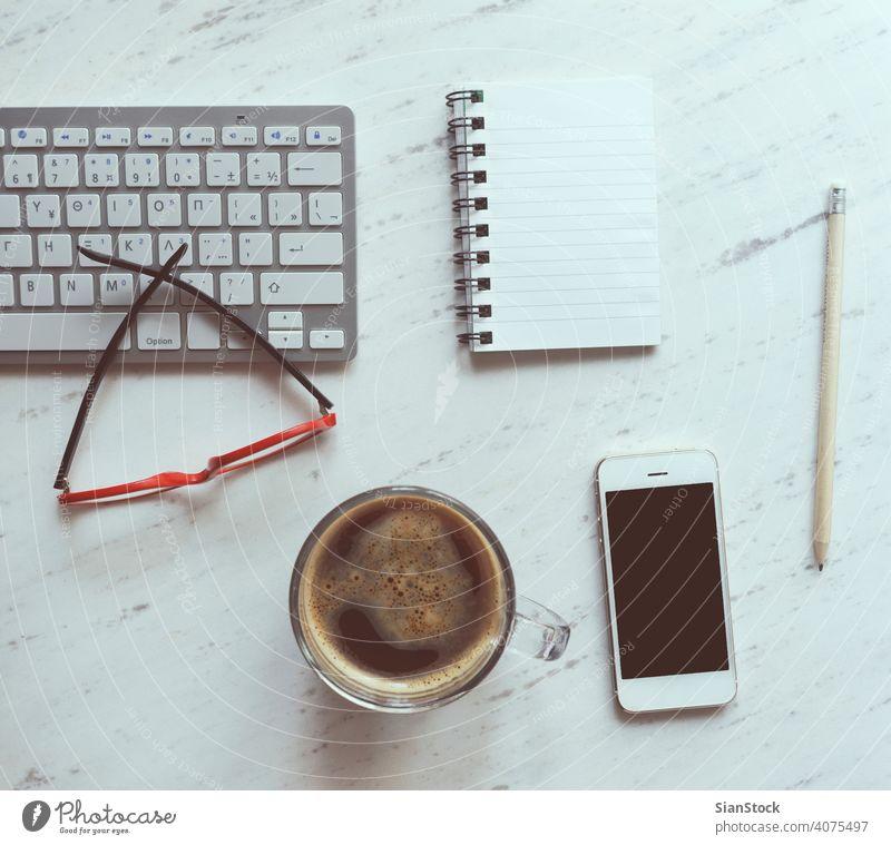 Arbeitsplatz mit Notebook, Kaffee, Smartphone, Brille und Tastatur. Laptop Top Schreibtisch Ansicht Tisch Büro Computer Tasse Desktop weiß Keyboard oben