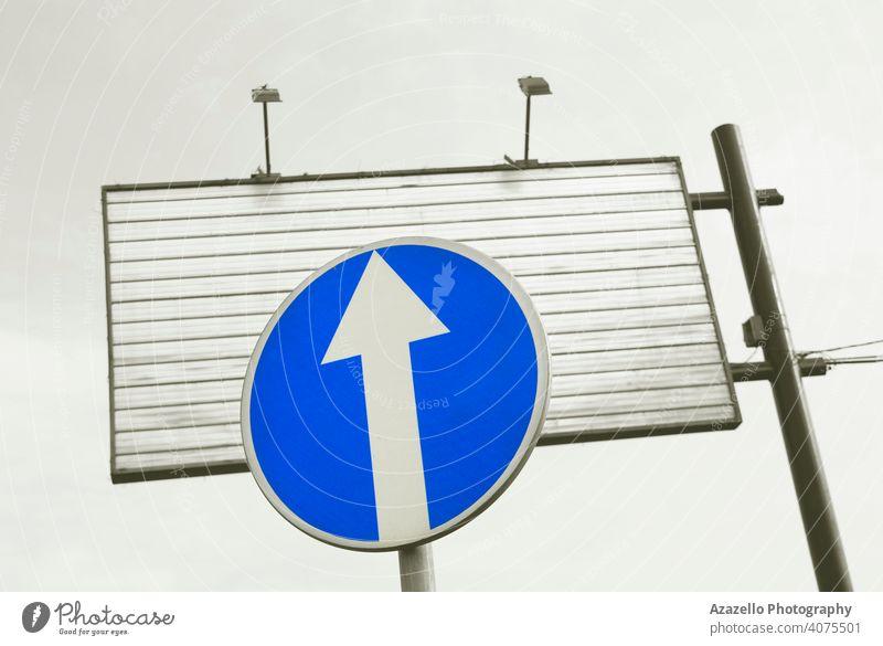 Blaues Verkehrsschild und eine leere Werbetafel aus Metall. Großstadt urban Inserat vor wach Pfeil Hintergrund blau blaues Schild Vorsicht kreisen Konzept