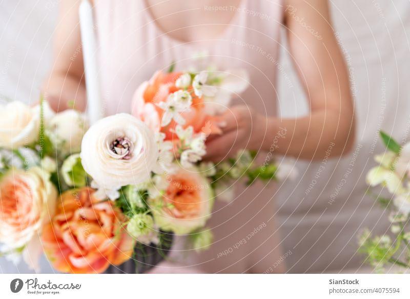 Frau berührt mit den Händen einen Blumenstrauß. Tisch jung Kaukasier Halt Beteiligung Hand Kleid weiß Vase Kerzen weich Licht Dekoration & Verzierung
