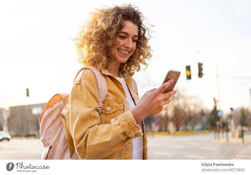 Schöne junge Frau mit lockigem Haar lächelnd und mit Smartphone natürlich Sonnenlicht urban Großstadt Hipster stylisch positiv sonnig cool Afro-Look Freude