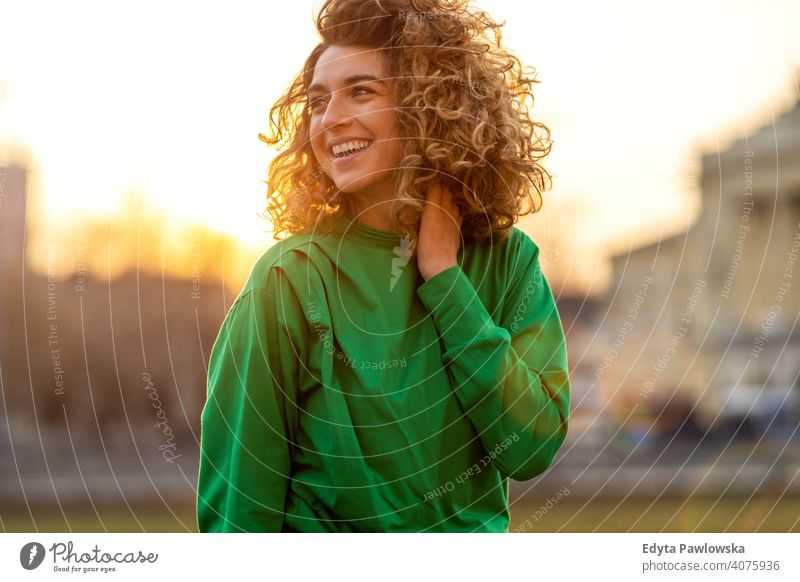 Porträt einer jungen Frau mit lockigem Haar in der Stadt natürlich Sonnenlicht urban Großstadt Hipster stylisch positiv sonnig cool Afro-Look Freude Gesundheit