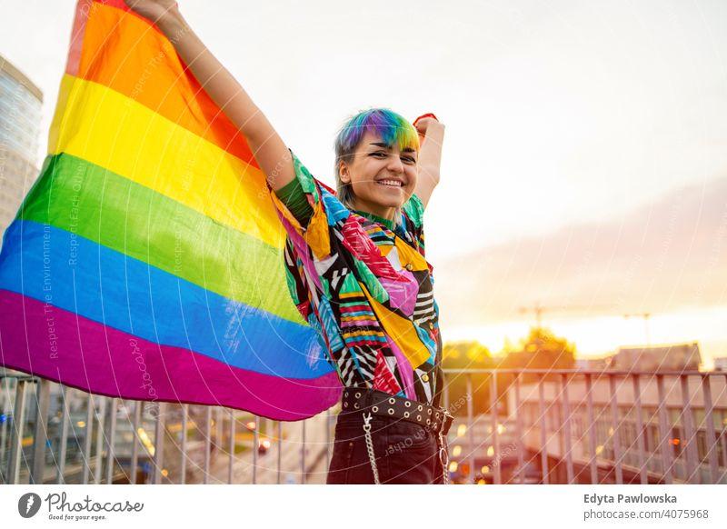 Porträt einer glücklichen nicht-binären Person, die eine Regenbogenflagge schwenkt geschlechtsfluid Gender-Fluidität lgbt Gleichstellung Homosexualität lesbisch