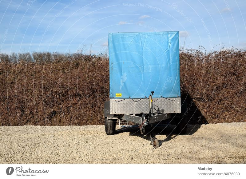 PKW Anhänger mit hoher blauer Plane aus Kunststoff vor spröder Hecke und blauem Himmel auf Kies in Naturfarben in Lemgo bei Detmold in Ostwestfalen-Lippe