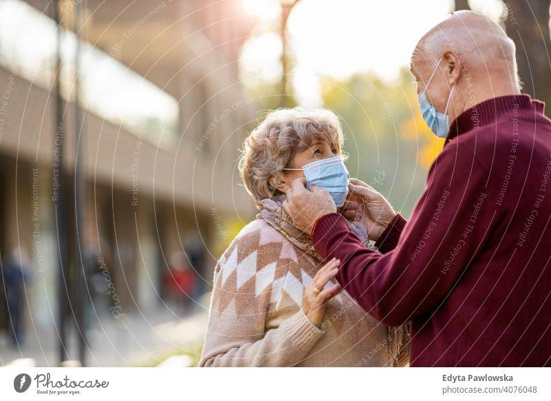 Älteres Ehepaar trägt Gesichtsschutzmasken im Freien Senior Paar Liebe echte Menschen in den Ruhestand getreten Rentnerin gealtert Großmutter Großeltern
