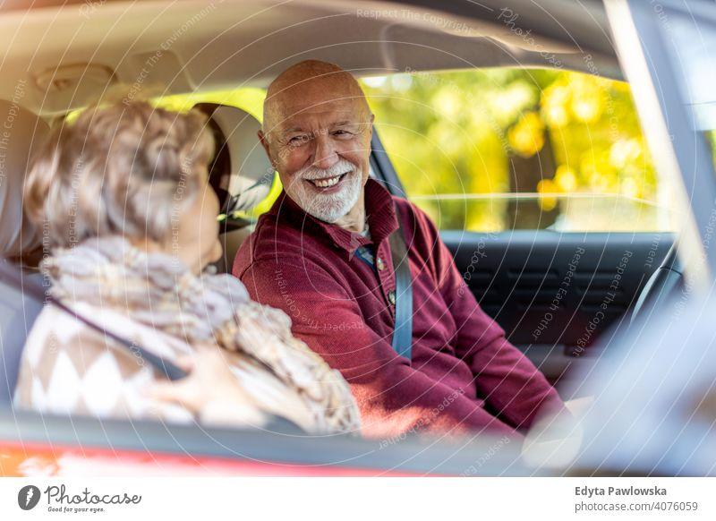 Happy Senior Couple unterwegs in ihrem Auto PKW Fahrzeug Fahrer fahren Reise reisen Ausflug Straße Verkehr Paar Liebe echte Menschen in den Ruhestand getreten