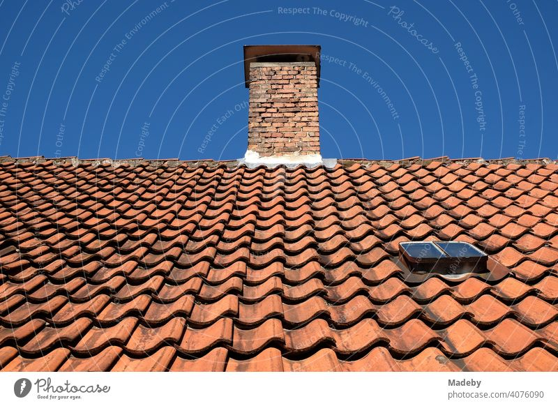 Rotbraune geschwungene Dachziegel auf dem Dach eines Altbau mit Schornstein im Sonnenschein in Oerlinghausen bei Bielefeld am Hermannsweg im Teutoburger Wald in Ostwestfalen-Lippe
