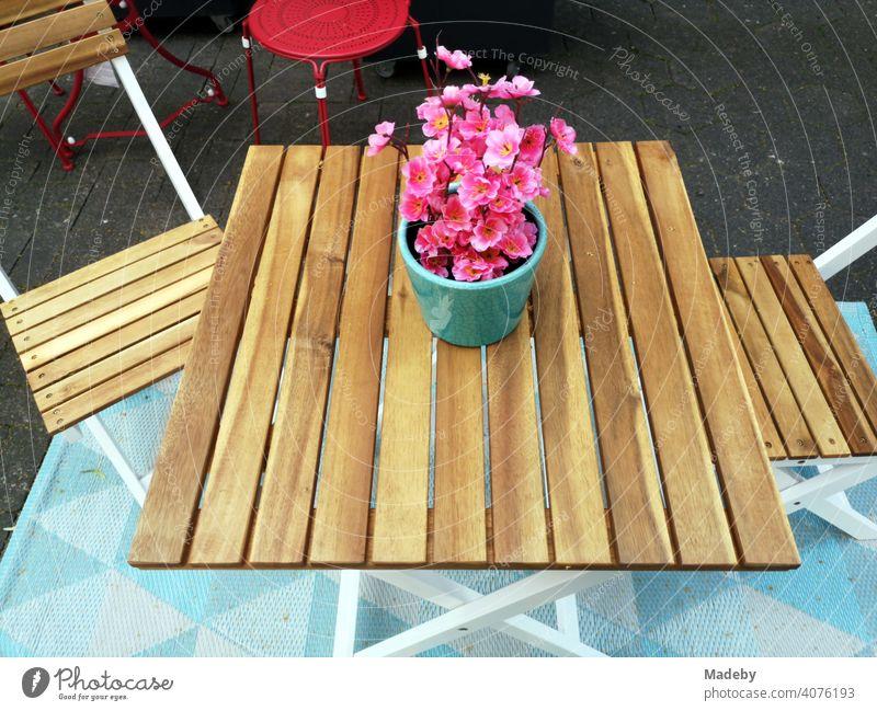 Gartentisch aus hellem Holz mit Bistrostühlen mit Blumentopf mit Pflanze mit rosa Blüten vor einem Geschäft in der Altstadt von Detmold in Ostwestfalen-Lippe