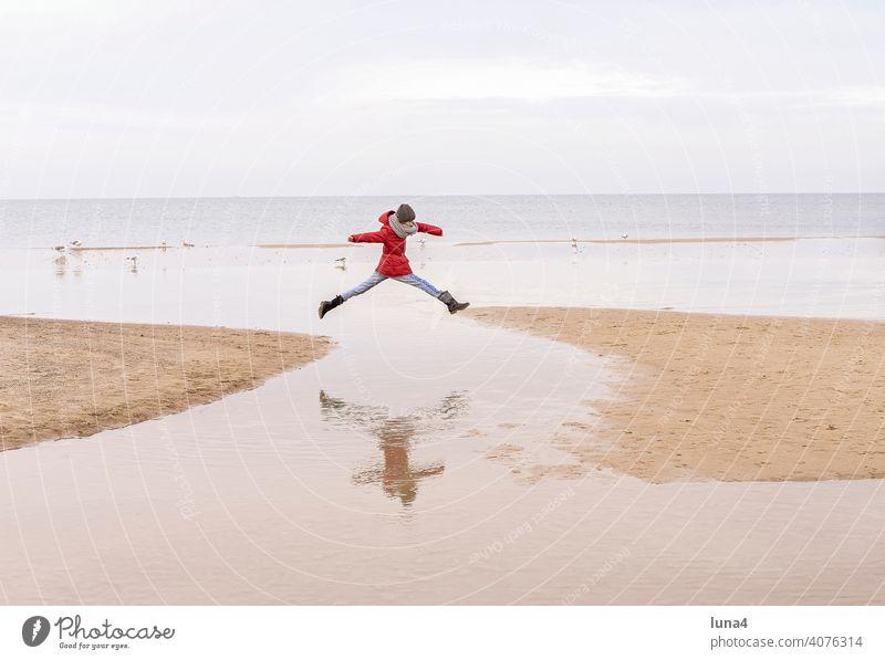 junges Mädchen springt am Stand springen Freudensprung Kind Strand Sprung Luftsprung Ostsee Freizeit Urlaub Ferien Herbst glücklich Lebensfreude fröhlich