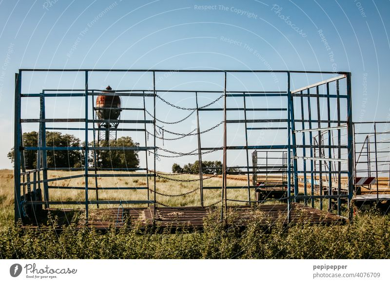 leerer Heuwagen bei der Ernte und im Hintergrund steht ein alter Wasserturm Feld Sommer Natur Landschaft Wiese Gras Stroh Ackerbau ländlich Bauernhof