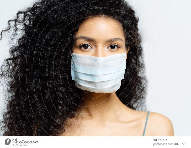 Ernste afroamerikanische Frau versucht, Virus und epidemische Krankheit zu stoppen, bleibt während des Ausbruchs der Infektion zu Hause, trägt medizinische Maske, isoliert auf weißem Hintergrund, wird ins Krankenhaus eingeliefert, diagnostiziert