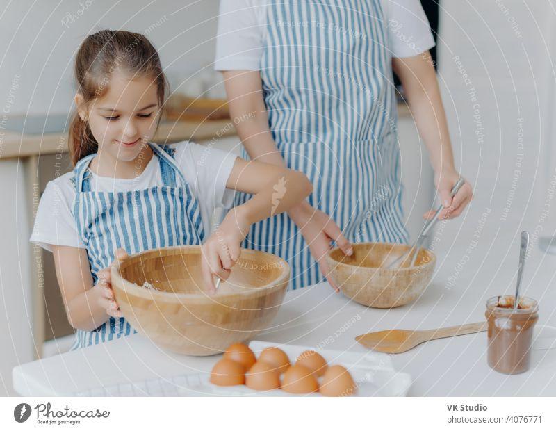 Mutter gibt kleinen Kind kulinarische Lektion, stehen nebeneinander, mischen Zutat in großen Holzschüsseln, machen Teig zusammen, verwenden Eier, Mehl und andere Produkte. Familie, Kochen, Mutterschaft