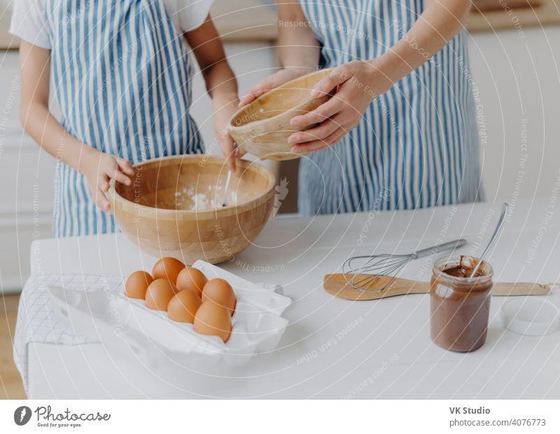 Cropped Bild von Müttern und Töchtern Hände mischen Zutaten, um Teig vorzubereiten und backen leckeres Gebäck, stehen in der Nähe von Küchentisch mit Eiern, geschmolzene Schokolade im Glas, tragen gestreiften blauen Schürzen