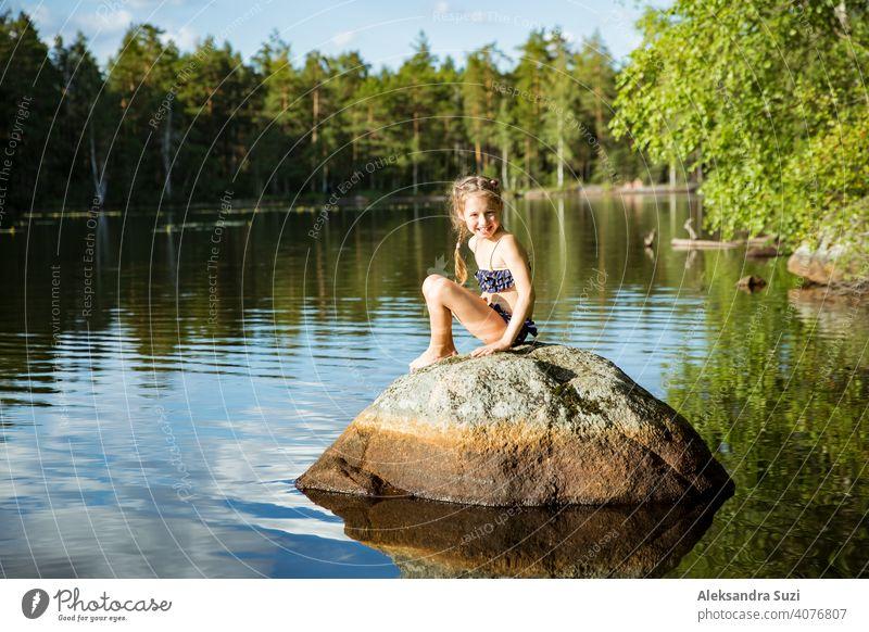 Nettes kleines Mädchen sitzt auf einem Felsen im See. Genießen Sie den Sommerurlaub. Kind und Natur. Glückliche Isolation Konzept. Finnland erforschen. Skandinavische Landschaft.