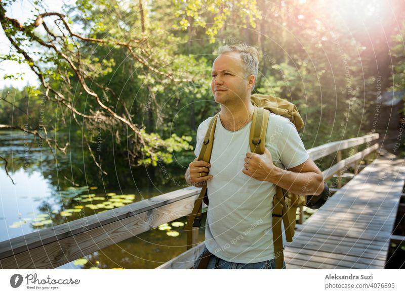 Reifer Mann erkundet die finnische Natur im Sommer, geht über die Brücke. Wanderer mit großen Rucksack Reisen in Wäldern. Sommer skandinavischen Landschaft von Seen und Wäldern.