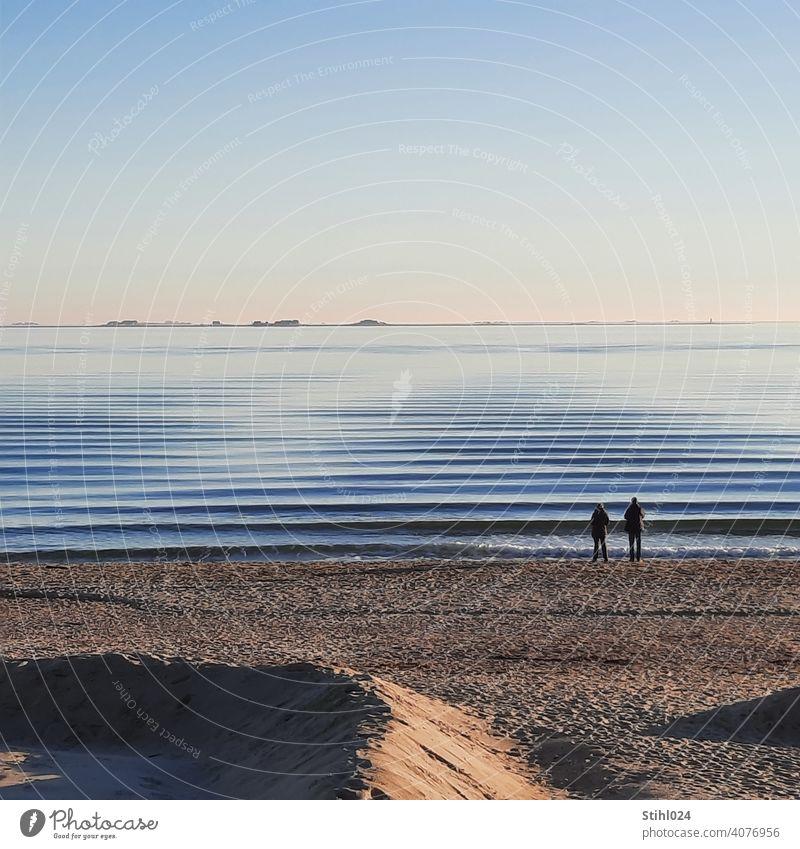 Paar am Strand von Föhr mit Blick auf die Halligen Sandstrand Wellen Wellengang Dünung sanft gekräuselt Wasser Ostsee Nordsee Insel Horizont