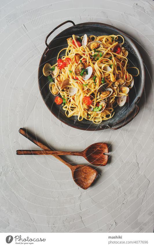 Pasta Spaghetti alle Vongole Meeresfrüchte-Nudeln mit Venusmuscheln in der Pfanne mit Kirschtomaten und Knoblauchsauce Muschel Panzer Lebensmittel roh frisch