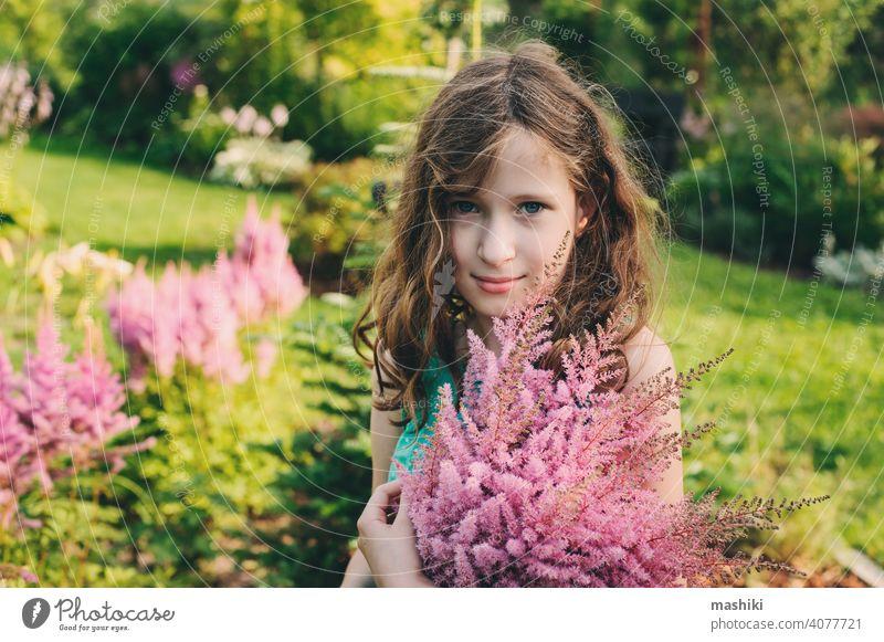 glückliches Kind Mädchen Kommissionierung Bouquet von Astilbe Blumen im Sommer Garten Natur Kindheit im Freien Glück Fröhlichkeit grün niedlich Spaß wenig