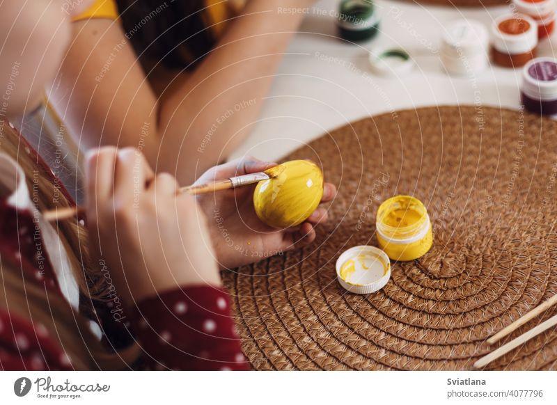 Kleine Blondine zu Hause in der Küche malt Ostereier in verschiedenen Farben für Ostern Frühling Kind Feiertag Vorbereitung Schwestern Bruder Ei hell Familie