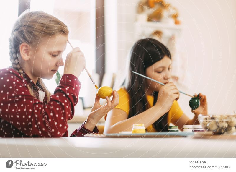 Zwei Schwestern sitzen am Tisch und bemalen Ostereier in verschiedenen Farben für Ostern, Nahaufnahme Frühling Kind Feiertag Vorbereitung Ei hell Familie