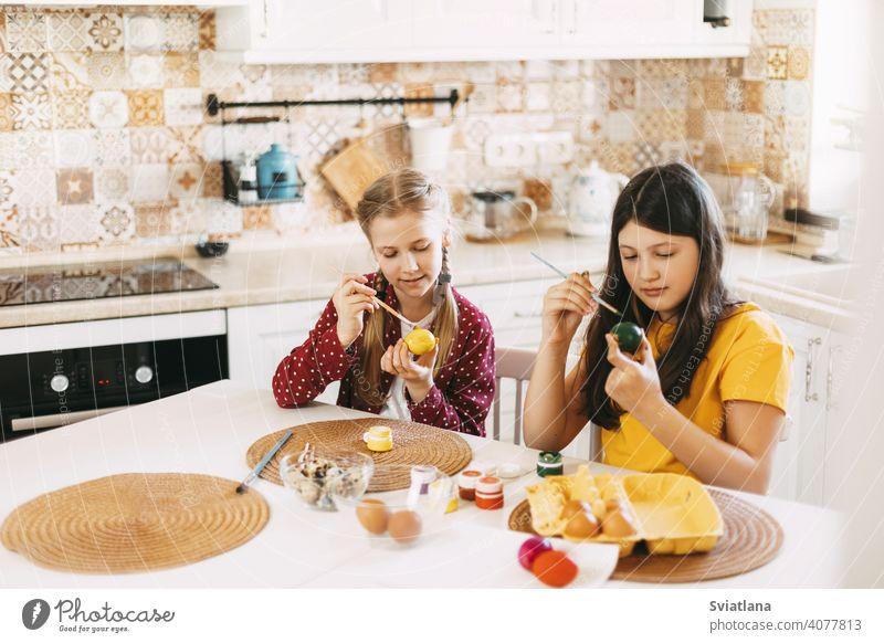 Zwei Schwestern sitzen am Tisch und malen Ostereier in verschiedenen Farben für Ostern Frühling Kind Feiertag Vorbereitung Ei hell Familie Mädchen weiß