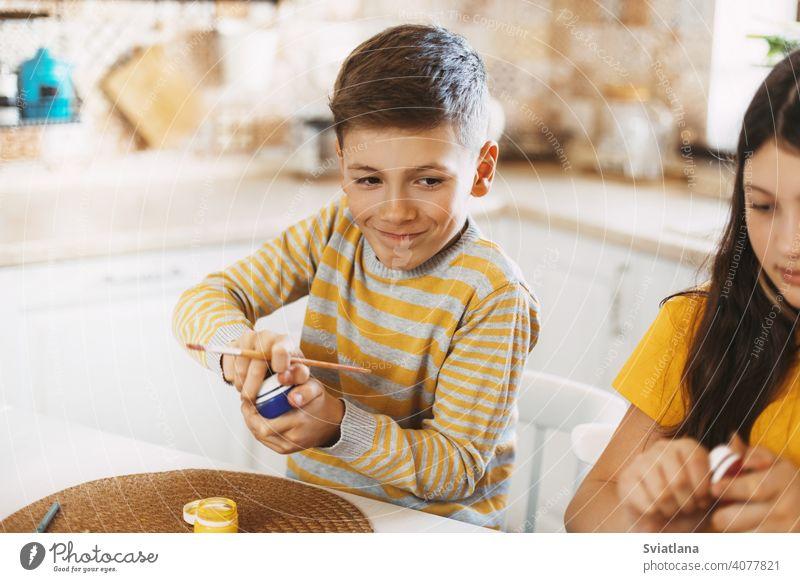 Konzentriertes Kind malt Ostereier in verschiedenen Farben für Ostern Frühling Feiertag Vorbereitung Schwestern Bruder Ei hell Familie verwöhnend Fröhlichkeit