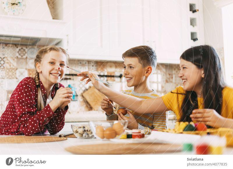 Zwei Schwestern und ein Bruder sitzen am Tisch und bemalen Ostereier in verschiedenen Farben für Ostern, lachen und schwelgen Frühling Kind Feiertag