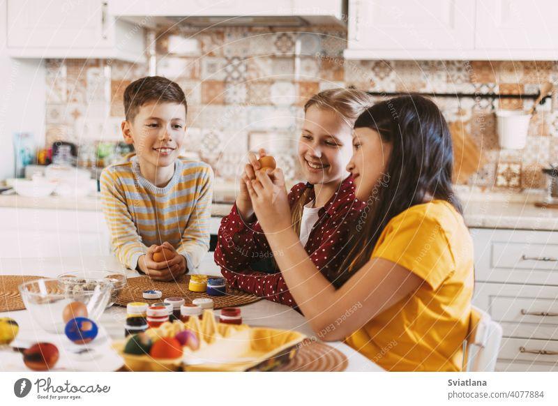 Lustige und fröhliche Kinder sitzen am Tisch malen Ostereier in verschiedenen Farben für Ostern Frühling Feiertag Vorbereitung Schwestern Bruder Ei hell Familie