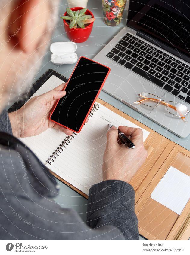 Mann schreibt MONTAG in Agenda und benutzt Handy auf einem grauen Bürotisch Nahaufnahme Business Hände schreiben intelligentes Arbeiten Laptop Planer