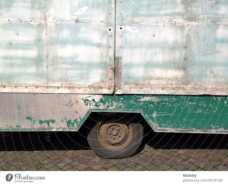 Umgebauter alter Wohnwagen mit deutlichen Gebrauchsspuren im Sonnenschein auf dem Marktplatz in Oerlinghausen bei Bielefeld am Hermannsweg im Teutoburger Wald in Ostwestfalen-Lippe