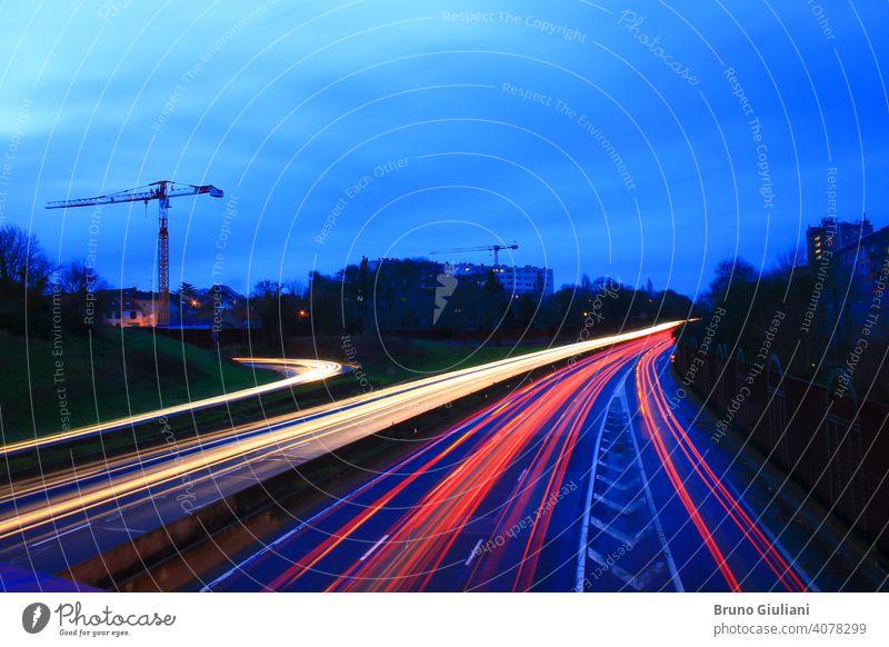 Leichte Spur von Autos auf einer Autobahn während des Morgens. Geschleuderte Fahrzeuge auf der Straße, gesehen von einer Brücke. Lightpainting-Szene. Gebäude