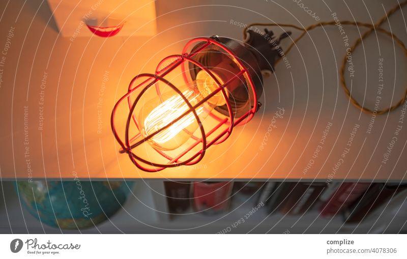 Vintage Bunkerlampe auf Sideboard Lichterscheinung Kunstlicht Nacht Dämmerung Textfreiraum rechts Textfreiraum links Innenaufnahme Gitter Glühbirne retro Holz