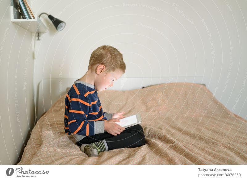 Junge mit Tablette auf dem Bett Kind Internet Technik & Technologie Lernen modern heimwärts digital Freizeit Bildung digitales Tablett Mitteilung Kindheit