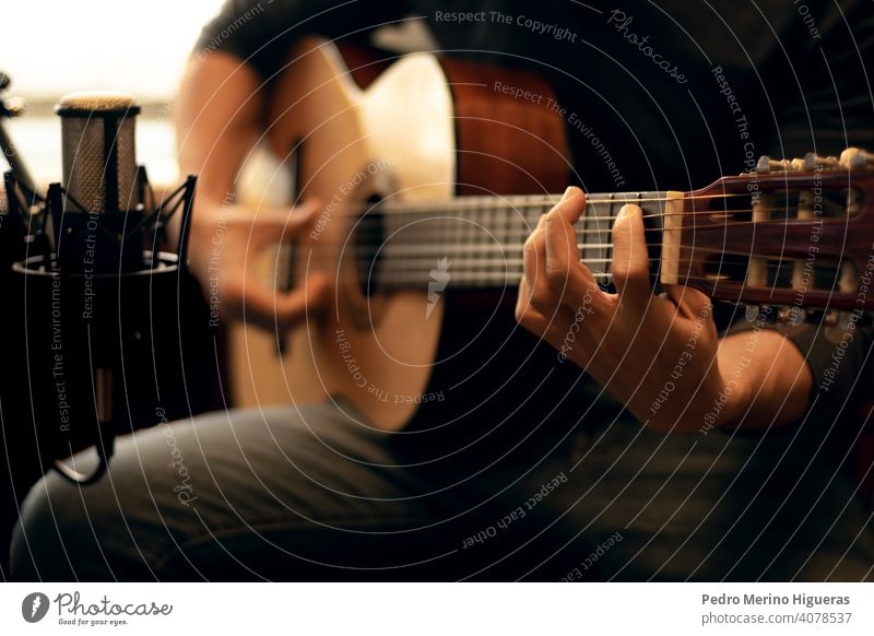 Mann spielt eine spanische Gitarre und nimmt mit einem Mikrofon auf Gitarrenspieler akustisch Musik Felsen Musical spielen Entertainment männlich Gesang Musiker