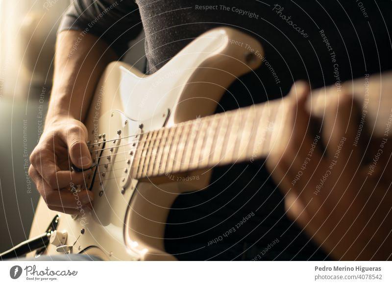 Mann spielt eine weiße E-Gitarre. Nahaufnahme Musik heimwärts Instrument männlich Musiker Gitarrenspieler spielen elektrisch Erwachsener Musical jung Spielen