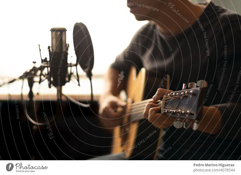 Mann spielt spanische Gitarre und singt, während er sie mit einem Mikrofon aufnimmt Musical Instrument Spanisch Musik männlich Person Gesang Menschen spielen