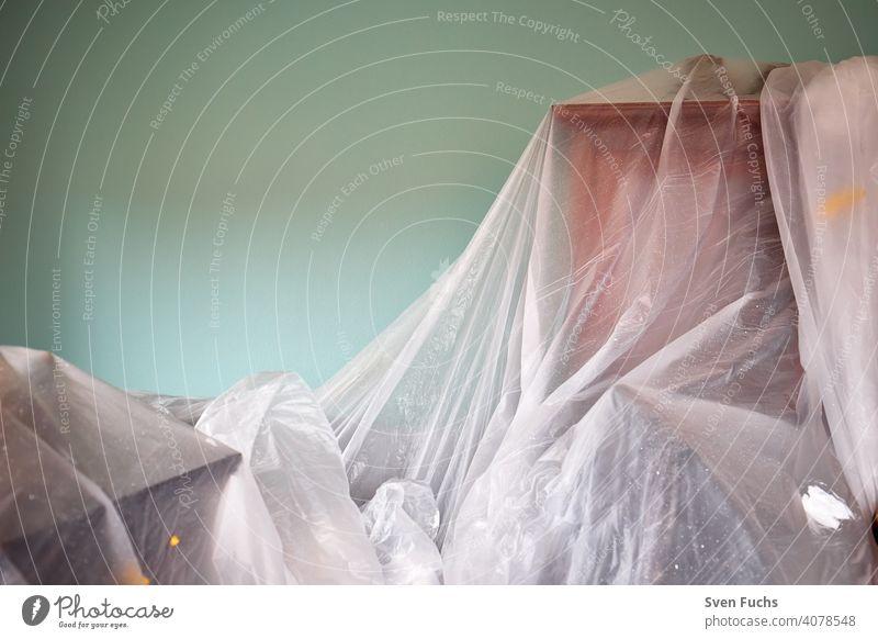 Wohnraum während einer Renovierung. Renovierung, Malerarbeiten, Folie, Schrank, Mobiliar, abgedeckt, Wohnraum Wand Tapete Grün Gelb Weiß renovierung