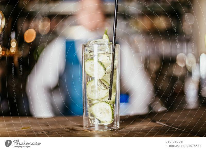 Cocktail mit Barkeeper im Hintergrund Cocktailbar Cocktailglas Gurke lemon Glas Getränk Longdrink Alkohol Spirituosen Erfrischungsgetränk Nachtleben