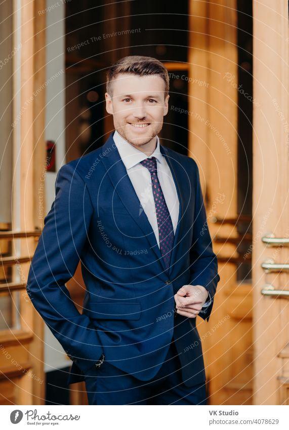 Attraktiver männlicher Manager in formellem Outfit, hält die Hand in der Tasche, hat einen positiven Gesichtsausdruck, steht in der Nähe von Büro, freut sich über gute Leistung, zuversichtlich im Erfolg. Männlicher Anwalt steht in der Nähe von Türen