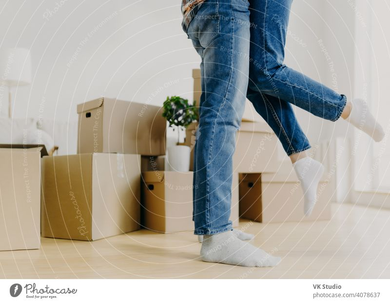 Gesichtsloses junges Paar zieht in ein neues Haus, Mann hebt Frau, haben Spaß, umgeben mit ausgepackten Kartons, beginnen neues Leben in kürzlich gekauften Wohnsitz. Familie, Umzug und Umzugstag Konzept
